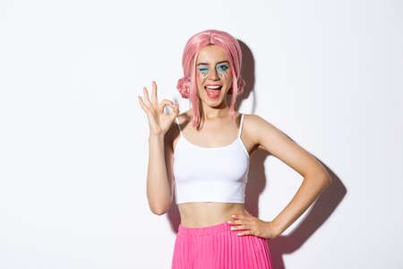 Beautiful cheeky girl in halloween costume and pink wig, showing okay sign in approval and winking, assure or recommend something, standing over white background