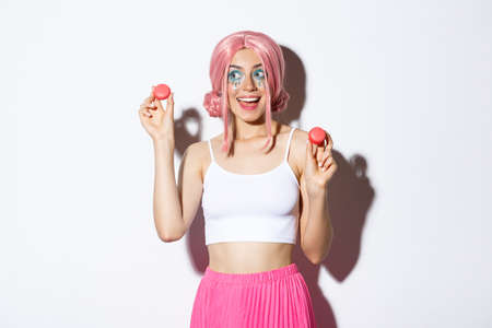 Portrait of silly beautiful caucasian girl in pink anime wig, showing macaroons and looking tempted aside, standing over white background Imagens