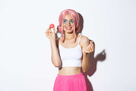 Portrait of lovely female model eating macaroons and smiling, wearing pink wig and outfit for party, standing over white background