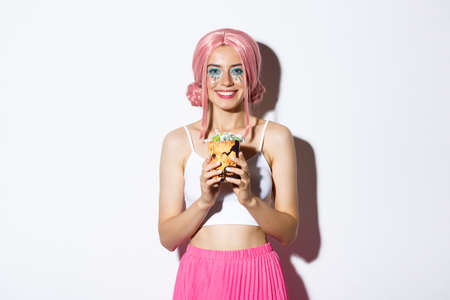 Image of beautiful smiling girl in pink wig holding trick or treat sweets, celebrating halloween, standing over white background