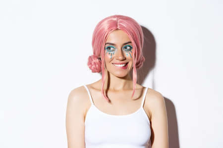 Close-up of coquettish pretty girl in pink wig, biting lip and looking at something tempting, standing over white background