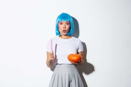 Concept of halloween. Portrait of surprised asian female holding pumpkin and candle, wearing blue wig, gasping amazed as standing over white background