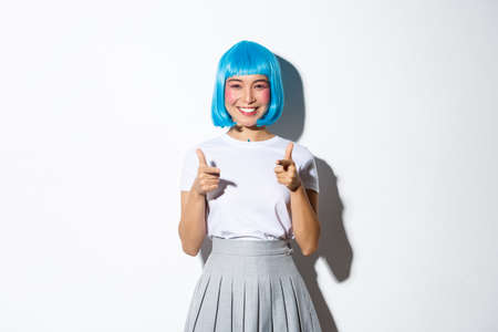 Cheeky japanese girl in blue party wig pointing fingers at camera and smiling, celebrating halloween, standing over white background