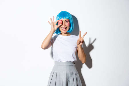 Beautiful japanese girl in blue wig and schoolgirl costume holding macaron, showing peace gesture and smiling, standing over white background