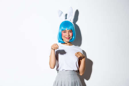 Portrait of beautiful silly japanese girl in blue wig and rabbit ears, dressed-up for halloween party, smiling coquettish, standing over white background
