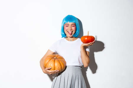 Happy attractive japanese girl in blue party wig, close eyes and showing tongue joyfully, celebrating halloween, holding two pumpkins
