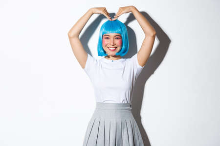Portrait of cute japanese girl in blue wig showing heart gesture and smiling, standing over white background