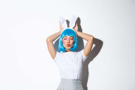 Lovely asian girl in blue short wig and rabbit ears, pouting coquettish and posing over white background in halloween costume Reklamní fotografie