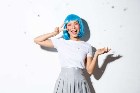 Portrait of happy asian girl in blue wig celebrating halloween, throwing confetti and showing kawaii peace gesture, standing over white background Archivio Fotografico