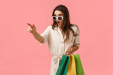Check this out, must have this season. Astonished and excited young enthusiastic female shoppaholic, seeing amazing thing on aisle, holding shipping bags and pointing finger left, pink background
