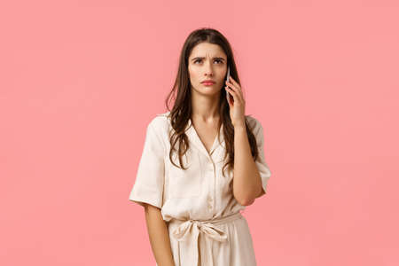 Serious and stressed young brunette woman hearing something strange, waiting someone pick-up phone, standing over pink background in dress, holding smartphone near ear, pink background