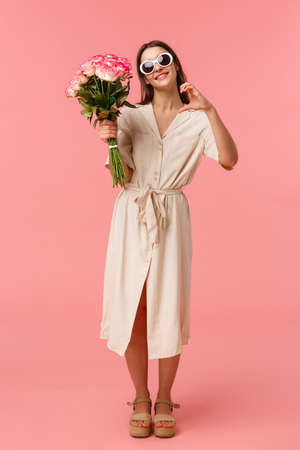 Full-length vertical portrait romantic and sensual, coquettish young woman holding bouquet flowers and make heart sign, expressing affection being touched and grateful with roses, pink background