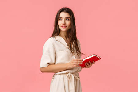 Attractive dreamy and romantic cute girl in dress turn around looking camera thoughtful, holding notebook, prepare notes for work, standing pink background, thinking