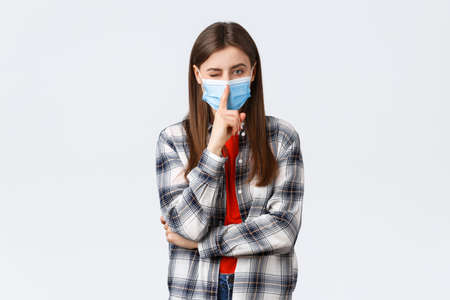 Coronavirus outbreak, leisure on quarantine, social distancing and emotions concept. Attractive young woman in checked casual shirt and medical mask ask keep secret, press finger to lips shush
