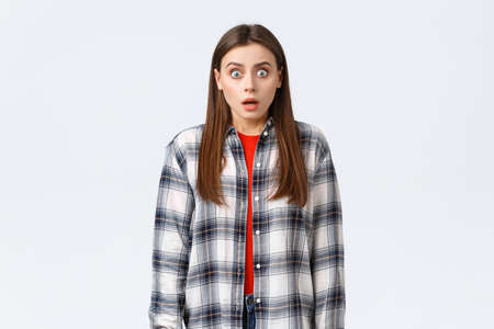 Lifestyle, different emotions, leisure activities concept. Shocked and scared, startled young woman in checked casual shirt, staring terrified, see something scary, standing in stupor