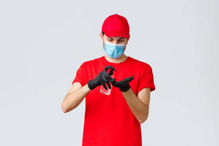 Takeaway, food and groceries delivery, covid-19 contactless orders concept. Courier or employee in red t-shirt and cap uniform, wear face mask and rubber gloves, apply hand sanitizer