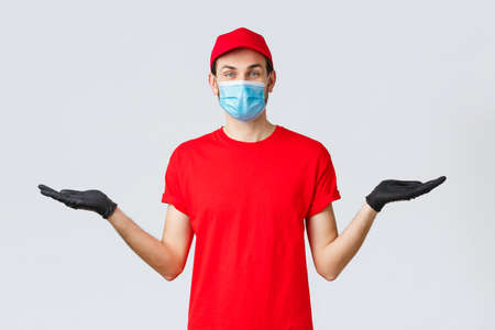 Groceries and packages delivery, covid-19, quarantine and shopping concept. Friendly delivery man in red uniform, face mask and gloves, holding two items or banners in hand, advice bonuses