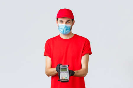 Contactless delivery, payment and online shopping during covid-19, self-quarantine. Pleasant delivery man in face mask and gloves, wear red uniform, giving paying terminal POS to pay for order 免版税图像