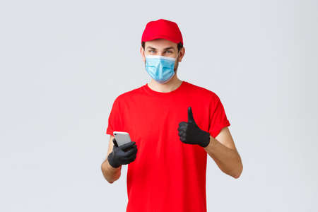 Contactless delivery, payment and online shopping during covid-19, self-quarantine. Friendly courier in gloves and red uniform cap, face mask, show thumb-up as recommend smartphone app or site 免版税图像