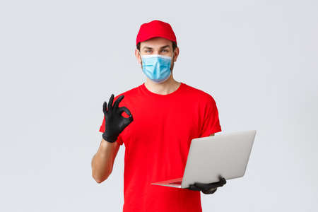 Customer support, covid-19 delivery packages, online orders processing concept. Smiling courier in face mask and gloves guarantee safety of parcel, processing order, show okay sign, hold laptop
