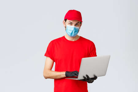 Customer support, covid-19 delivery packages, online orders processing concept. Pleasant delivery guy in red uniform, face mask and gloves, using laptop and look camera, processing order