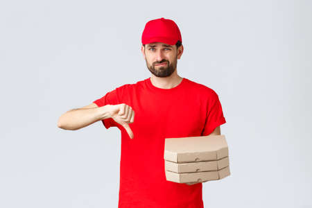 Food delivery, quarantine, stay home and order online concept. Disappointed and reluctant courier in red uniform cap and t-shirt, dislike pooq quality fast-food, thumb-down, holding pizza 免版税图像