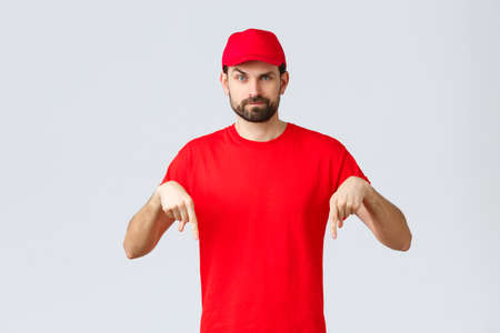 Online shopping, delivery during quarantine and takeaway concept. Skeptical or suspicious courier in red uniform cap and t-shirt, pointing fingers down, standing grey background 免版税图像