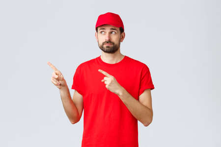Online shopping, delivery during quarantine and takeaway concept. Uncertain and displeased, reluctant courier, employee in red t-shirt and cap, smirk disappointed pointing fingers upper left corner 免版税图像
