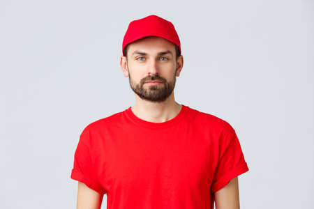 Online shopping, delivery during quarantine and takeaway concept. Young handsome bearded courier in red service uniform with cap and t-shirt, employee working transfering orders