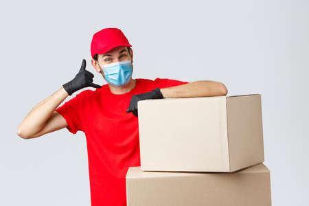 Packages and parcels delivery, covid-19 quarantine and transfer orders. Friendly courier in red uniform, face mask and gloves asking customer give call, show phone sign, stand near boxes