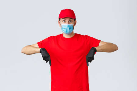 Covid-19, self-quarantine, online shopping and shipping concept. Surprised delivery guy in uniform pointing fingers down, showing promo. Courier in medical mask, gloves work with clients 免版税图像