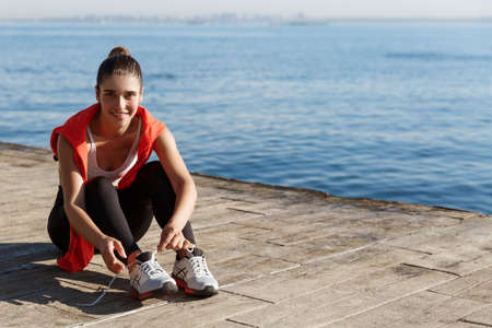 Outdoor shot of attractive smiling sportswoman sitting on pier and tying shoelaces during workout, training near the sea
