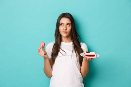 Image of thoughtful brunette woman, making choice between desserts, holding macaroon and cake, standing over blue background