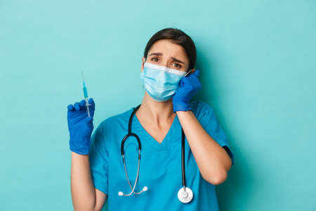 Concept of covid-19 and quarantine concept. Close-up of compassionate beautiful female doctor in medical mask, gloves and scrubs, holding syringe and looking worried