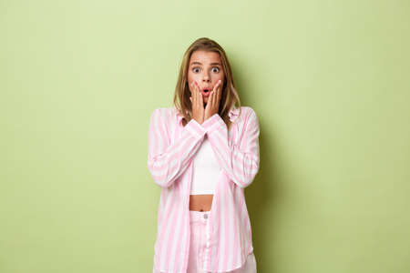 Portrait of shocked blond girl in pink outfit, gasping and looking nervous, standing alarmed against green background