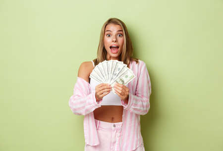 Image of excited girl winning prize, holding money and smiling surprised, standing over green background