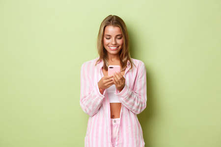 Image of beautiful blond woman in pink shirt, looking at mobile phone and smiling, standing over green background
