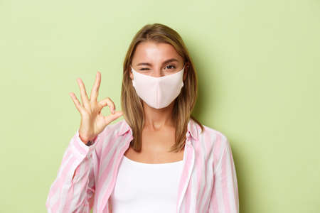 Concept of quarantine, coronavirus and lifestyle. Close-up of cheeky blond girl in face mask, recommend something, winking and showing okay sign, standing over green background
