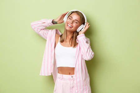 Portrait of stylish blond woman in pink shirt, with tattoos, listening to music in headphones with pleased smile, standing over green background