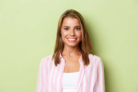 Close-up of beautiful smiling woman with blond short hair, looking happy and confident, standing over green background
