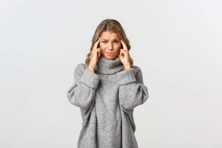 Image of upset blond girl feeling bad, touching head and grimacing, have headache or trying to think, standing over white background Reklamní fotografie