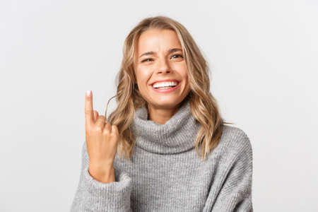 Close-up of carefree blond girl in grey sweater, showing one finger and smiling, standing over white background
