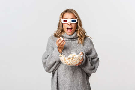 Image of thrilled blond girl in grey sweater and 3d glasses, holding bowl with popcorn, and gasping amazed while watching movie, standing over white background