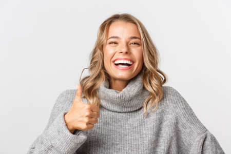 Close-up of happy blond girl in grey sweater, showing thumbs-up and smiling, like something, standing over white background