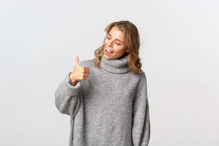 Portrait of cute blond girl in grey sweater, looking at her thumb-up and smiling, standing over white background