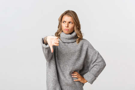Young skeptical woman frowning and looking away, showing thumb-down, disappointed in something bad, standing over white background