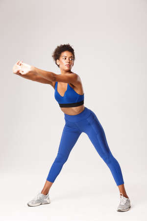 Full length of attractive african-american woman with fit body, wearing blue sportwear, exercising over white background, showing stretching warm-up workout, looking aside