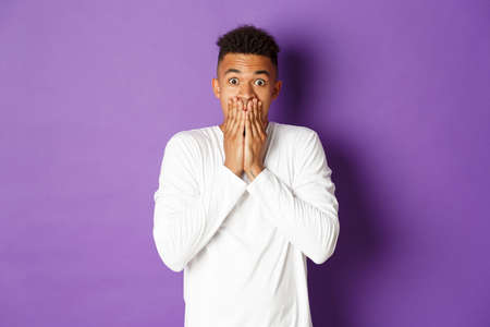 Image of shocked african-american hipster guy in white sweatshirt, gasping and looking startled, cover mouth with hands, standing over purple background Imagens