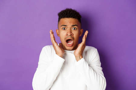 Closed-up of shocked and scared african-american man, gasping and looking startled at something bad, standing over purple background