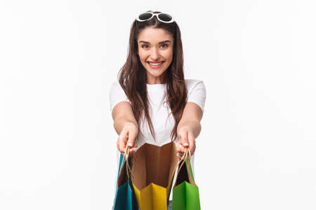 Shopping, leisure and lifestyle concept. Here take a look, its for you. Excited happy young woman sharing with friend, showing her what inside bag as buying lots of staff for vacation
